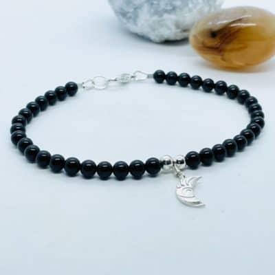 A black obsidian beaded bracelet, with a silver moon charm