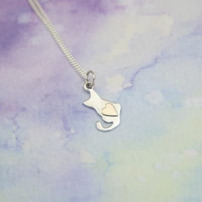 Silver cat pendant with a gold heart in the middle